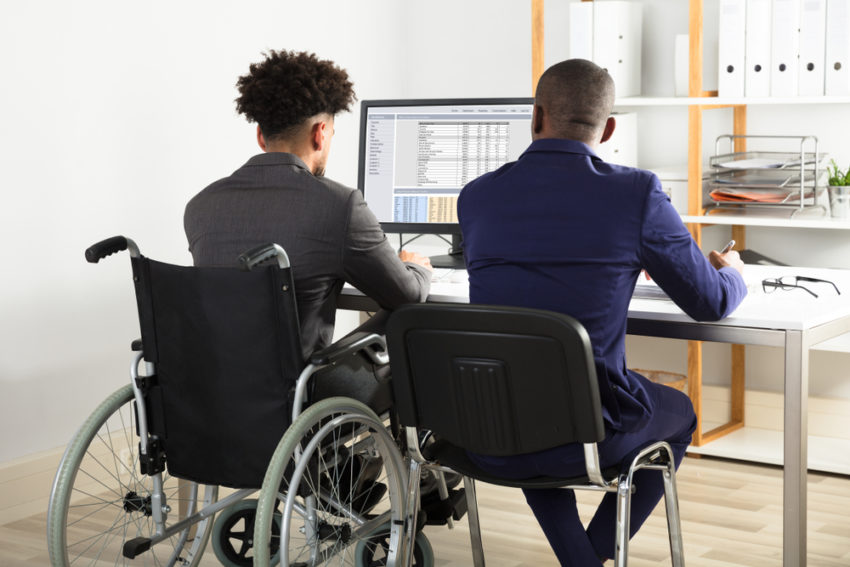 person in a wheelchair working at a desk